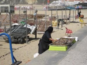 Troc kenfisch am Strand von Nazaré - aeltere Frauen in schwarzer Kleidung oder einer Art Tracht praegen hier noch das Ortsbild