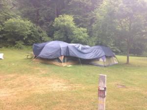 Hier zelten offenbar Camper mit Regenerfahrung - Gruppenkuscheln unter der zusätzlichen Plane